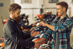 Men in motorbike salon. Handsome young bearded men in black leather jacket is buying a motorbike, attractive blond men is giving keys and handshaking Royalty Free Stock Photos