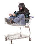 Men in motorcycle jacket sitting in shopping cart Stock Photo