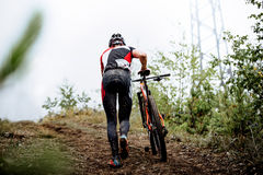 Men mountainbikers climb mountain. On foot with their bicycle during competitions in cross-country Royalty Free Stock Photos