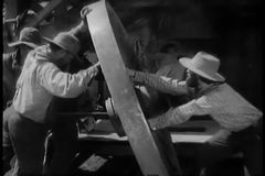 Men moving large wooden wheel stock footage