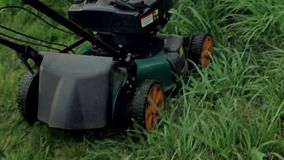Men mowing grass with a lawn mower stock footage