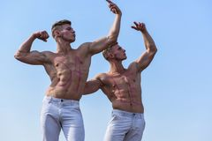 Men muscular with nude sexy torso, sky on background. Athletes with inscription sale on muscular chests. Sales concept. Athletes on serious faces demonstrating Royalty Free Stock Photos