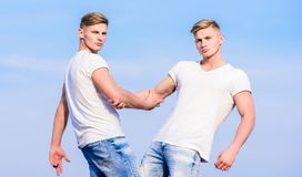 Men muscular twins brothers in white shirts sky background. Brotherhood concept. Benefits and drawbacks of having. Identical twin brother. Benefits of having royalty free stock photo