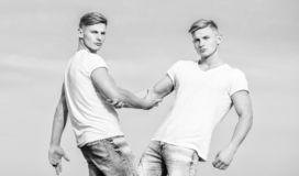 Men muscular twins brothers in white shirts sky background. Brotherhood concept. Benefits and drawbacks of having. Identical twin brother. Benefits of having stock image