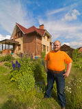 Men near his house. Self-satisfied man standing near his own house royalty free stock photo