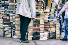 Men near of tall pile of old books in flea market, real street scene. Lifestyle in city, education, reading fiction. Men near of tall pile of old books in flea royalty free stock images