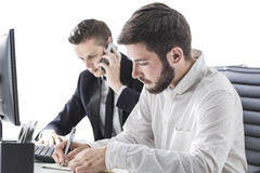 Men in office. Two business partners work in office. They sit at table. One is talking on his mobile phone. Second is making notes on paper. Concept of Royalty Free Stock Image