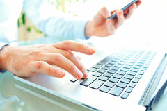 Men office worker typing on the keyboard and using smartphone. Male hands or man office worker typing on the keyboard and using smartphone Royalty Free Stock Photography