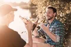 A man in a blue shirt sits on the river bank with a bottle of beer and tells something to the old man. A men and an old men are drinking beer on the river bank royalty free stock photography