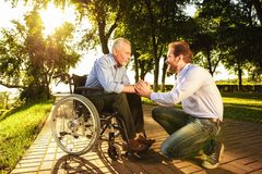 The old man in a wheelchair with his son in the park. They`re walking. A man is holding an old man by the hand. A men and an old men in a wheelchair are walking stock images
