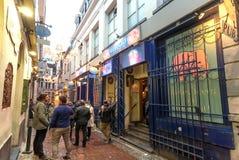 Men outside the popular bar on narrow historical street Stock Image