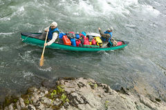 Men in overloaded canoe on Alaskan river rapids. Two men navigate an overloaded canoe through rapids and rocks during an adventure on a wild Alaskan river Royalty Free Stock Photo