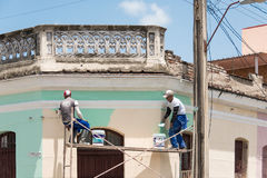 Men painting a facade of a colonial house. Stock Photography
