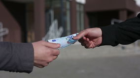 Men pass each other money euro banknotes and shake hands. Slow motion stock video