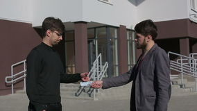 Men pass each other money euro banknotes and shake hands. Slow motion stock video footage