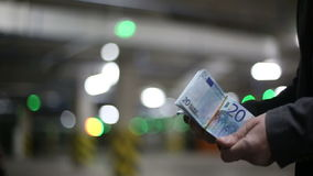 Men pass each other money euro banknotes and shake hands. Slow motion. Bokeh background stock footage
