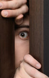 Men peeking. Close-up of man peeking through the open door royalty free stock photos