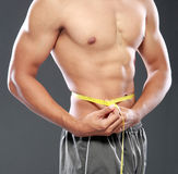 Men with perfect abs. Portrait of Men with perfect abs measuring his waist Stock Photos
