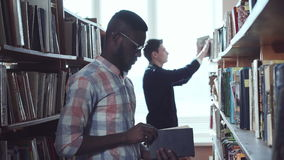 Men picking the books. Two young men standing in library and choosing the books stock video
