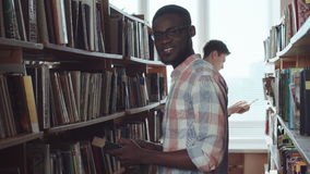 Men picking the books. Two young men standing in library and choosing the books. Then African student weared eyeglasses turn to camera and smile stock video footage
