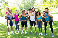 Men piggybacking female friends in the park Royalty Free Stock Images
