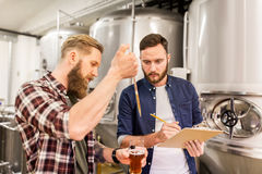 Men with pipette testing craft beer at brewery. Alcohol production, manufacture, business and people concept - men with pipette and clipboard testing craft beer Royalty Free Stock Photography