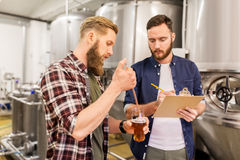 Men with pipette testing craft beer at brewery. Alcohol production, manufacture, business and people concept - men with pipette and clipboard testing craft beer Royalty Free Stock Image
