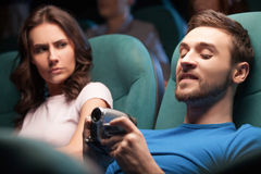 Men pirating. Young men pirating at the cinema while women looking at him royalty free stock images