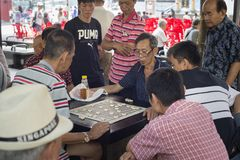 Men play checkers Chinatown Singapore. SINGAPORE - FEB 17, 2017: Men play checkers on a street of Chinatown district in Singapore. Ethnic Chinese began settling Stock Images