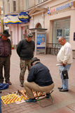 Men play chess on Arbat Street in Moscow,Russia. MOSCOW, RUSSIA - MAY 15, 2011: Local senior men play chess outdoor on the famous pedestrian Arbat Street in Stock Photography