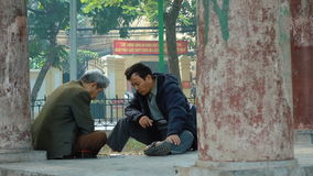 Men play chess in the park of Hanoi stock video