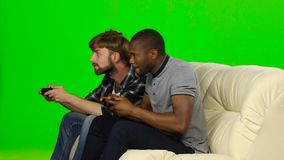 Men play on consoles with wireless joysticks. Green screen. Men play on the console in the same team and fighting for victory, two guys are playing emotional stock video