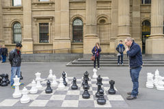 Men play giant outdoor chess game. Melbourne, Australia - August 1, 2015: Two men playing giant outdoor chess outside the State Library of Victoria in Melbourne Stock Images