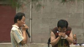 Men play on harmonica on streets of city. stock video