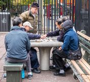 Men play mahjong in New York City Chinatown park Stock Image