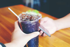 Men play smartphone and Woman hand. Giving glass of cola.Glass of cola ,Soft drinks with ice, sweethart or buddy Stock Photo