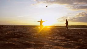 Men play volleyball on sand in sun, beach volleyball on summer evening. stock footage