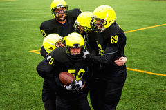 Men playing american football. Men in green sportswear and helmet playing american football on the sports ground Stock Photos