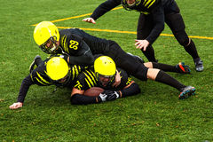 Men playing american football. Men in green sportswear and helmet playing american football on the sports ground Royalty Free Stock Photo