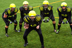 Men playing american football. Men in green sportswear and helmet playing american football on the sports ground Stock Photography