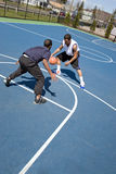 Men Playing Basketball. A young basketball player guarding his opponent during a one on one basketball game Royalty Free Stock Images