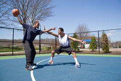 Men Playing Basketball. A young basketball player guarding his opponent during a one on one basketball game Stock Photos