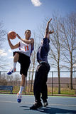 Men Playing Basketball. Two young basketball players compete fiercely against each other Stock Photos