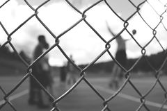 Men Playing Basketball Behind Silver Steel Fence Stock Image