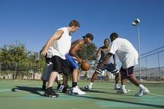 Men Playing Basketball On Court. Full length of young men playing basketball on court Stock Photo