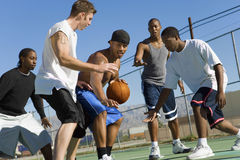 Men Playing Basketball On Court. Group of multiethnic men playing basketball on court Royalty Free Stock Photography
