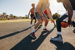 Men playing basketball. Game on a sunny day. Men practicing basketball skills in play area Stock Image