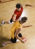 Men Playing Basketball On Indoor Court. High angle view of two young men playing basketball on indoor court Stock Image