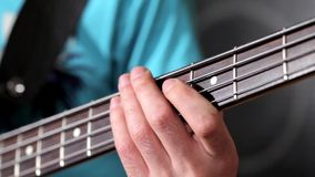 Men playing at bass guitar in music studio Royalty Free Stock Photography