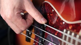 Men playing at bass guitar in music studio Stock Photography
